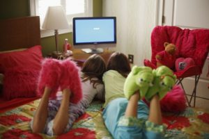 Girls Watching Flat Panel TV --- Image by © Pixelhouse/Corbis